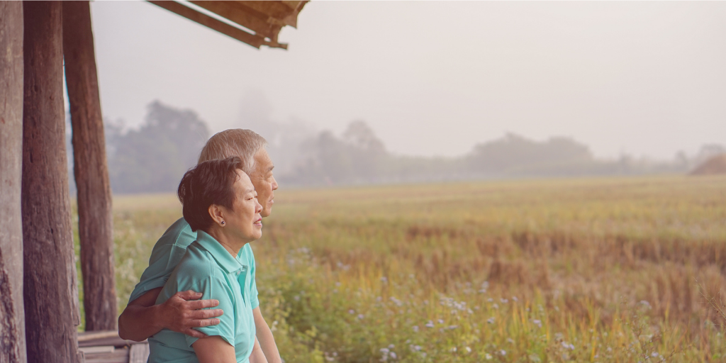 an elderly couple looking toward a farm field wistfully